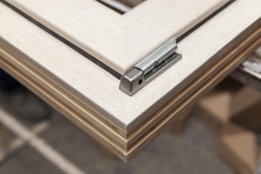 Vista angolare della cerniera di un serramento color legno naturale